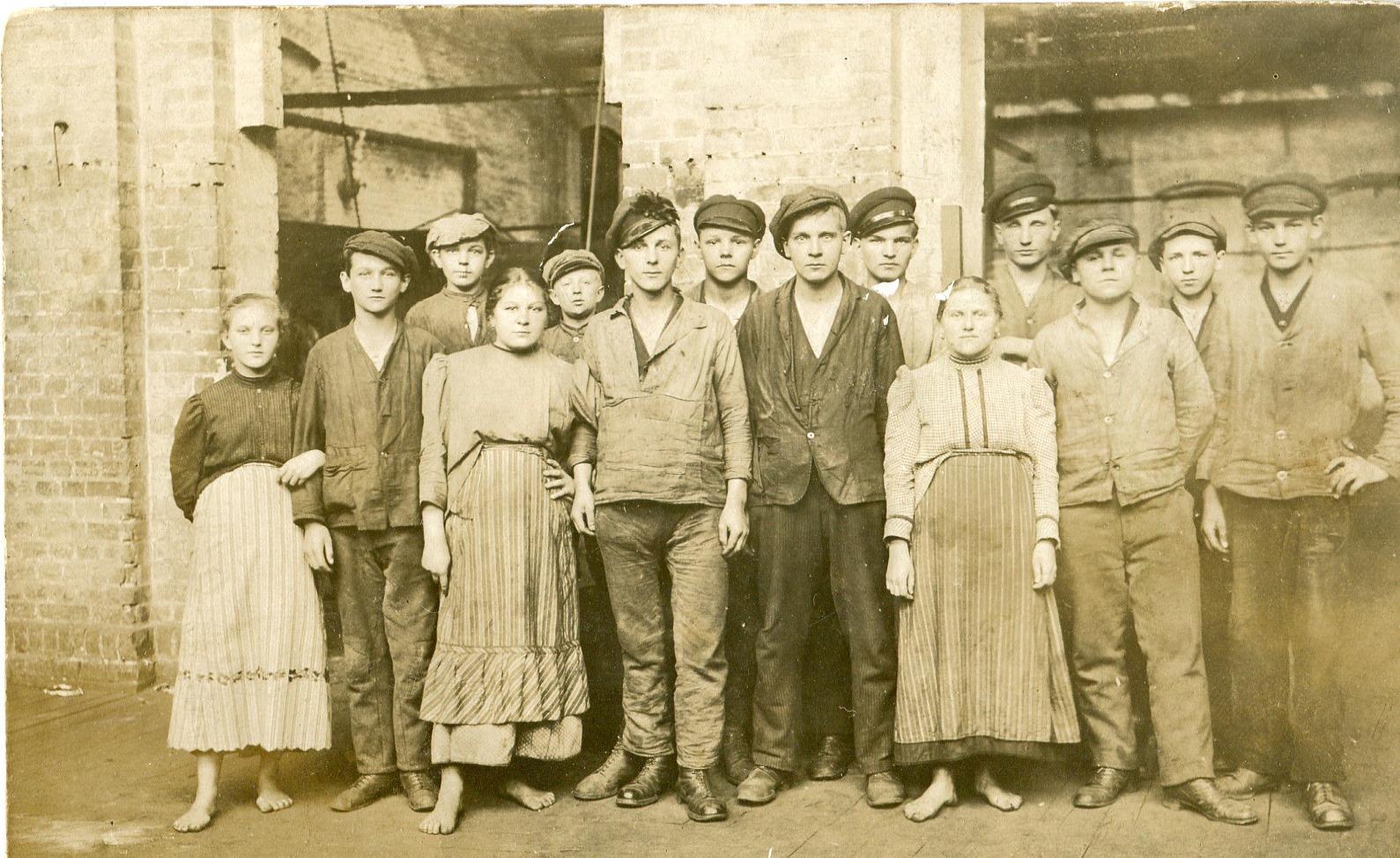 Fotografia grupy mężczyzn ikobiet wubraniach roboczych, zpocz. XX w. natle budynków przemysłowych
