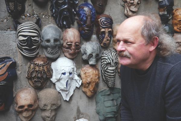 Portret Zbigniewa Mury natle ściany zmaskami ceramicznymi